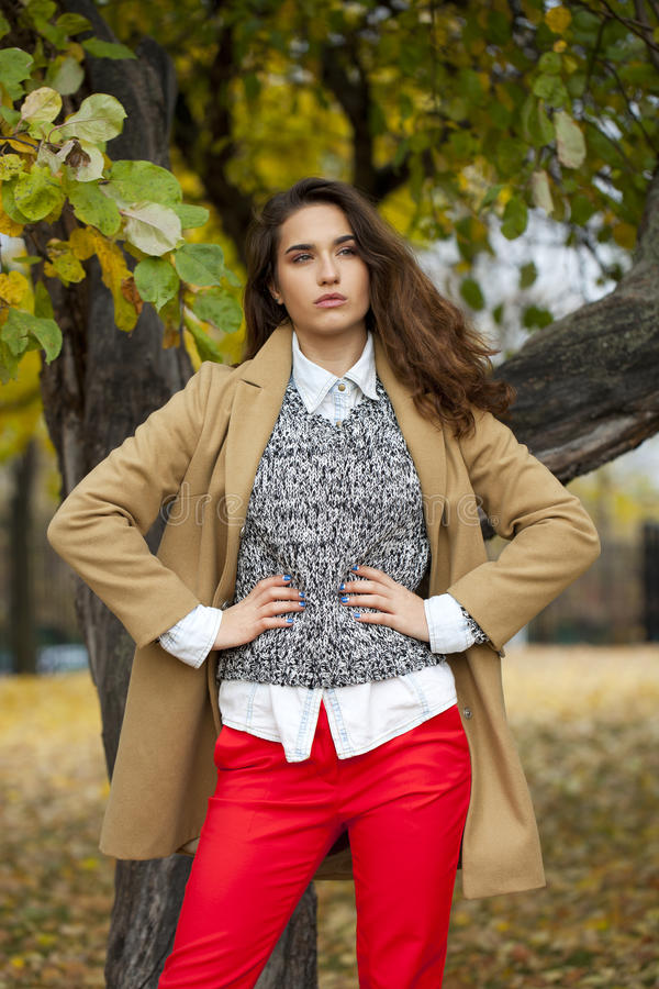 Jonge vrouw die in manierlaag in de herfstpark lopen stock foto