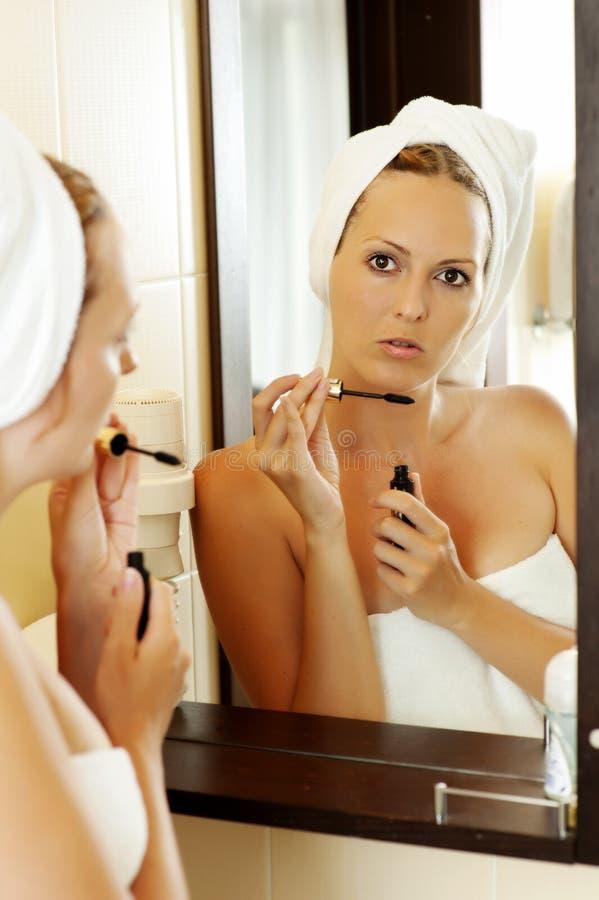 Jonge vrouw die mascara aanzet stock foto's
