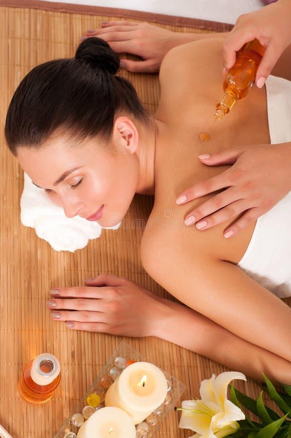 Jonge vrouw die massage in bamboo spa krijgt stock afbeeldingen