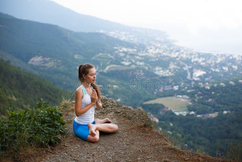 Jonge vrouw die, meisje die yogahoogte in de bergen doen, het concept van de ontspannings zelf-bezinning in openlucht mediteren royalty-vrije stock fotografie