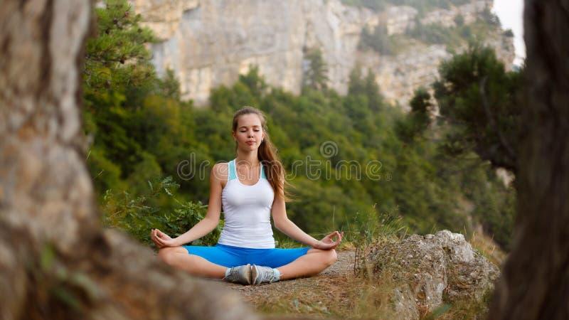 Jonge vrouw die, meisje die yogahoogte in de bergen doen, het concept van de ontspannings zelf-bezinning in openlucht mediteren stock foto