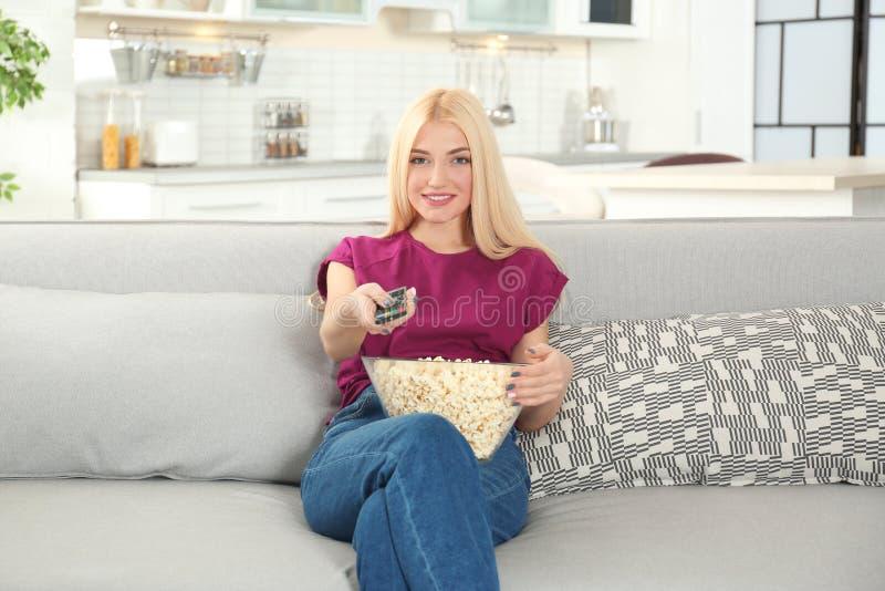 Jonge vrouw die met afstandsbediening en kom popcorn op TV op bank letten royalty-vrije stock foto