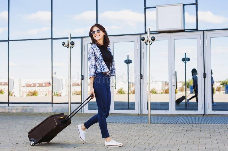 Jonge vrouw die met bagagekoffer, vakanties, reis en actief levensstijlconcept lopen stock fotografie