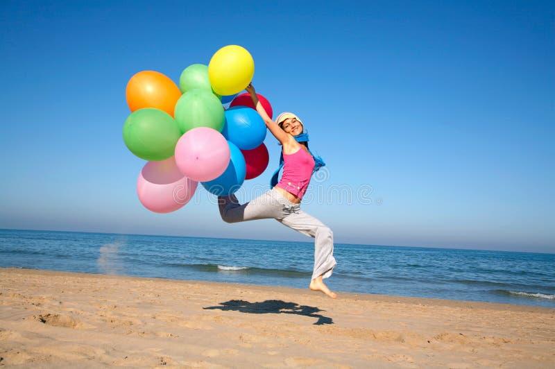 Jonge vrouw die met ballons op het strand springt royalty-vrije stock afbeeldingen
