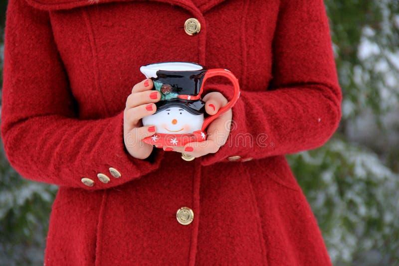 Jonge vrouw die met blondehaar in rode laag de leuke mok van de sneeuwmanvakantie houden royalty-vrije stock afbeelding