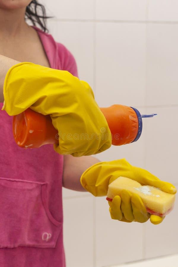 Jonge vrouw die met chemische schonere fles en spons wordt uitgerust Huishouden en het schoonmaken concept r stock afbeeldingen