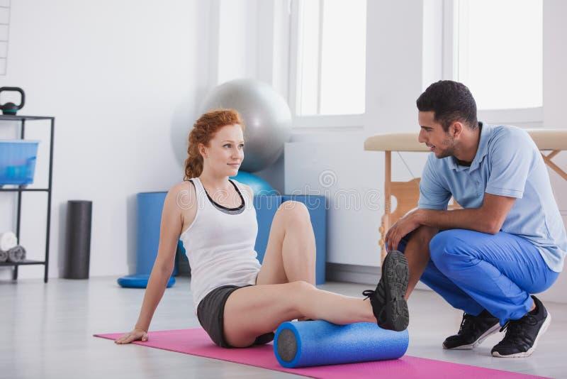 Jonge vrouw die met een schuimrol uitwerken die op een mat door haar trainer wordt gesteund royalty-vrije stock afbeelding