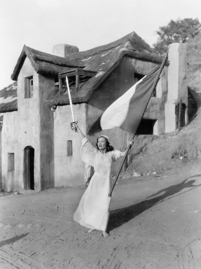 Jonge vrouw die met een vlag en een zwaard lopen (Alle afgeschilderde personen leven niet langer en geen landgoed bestaat Leveran stock afbeeldingen