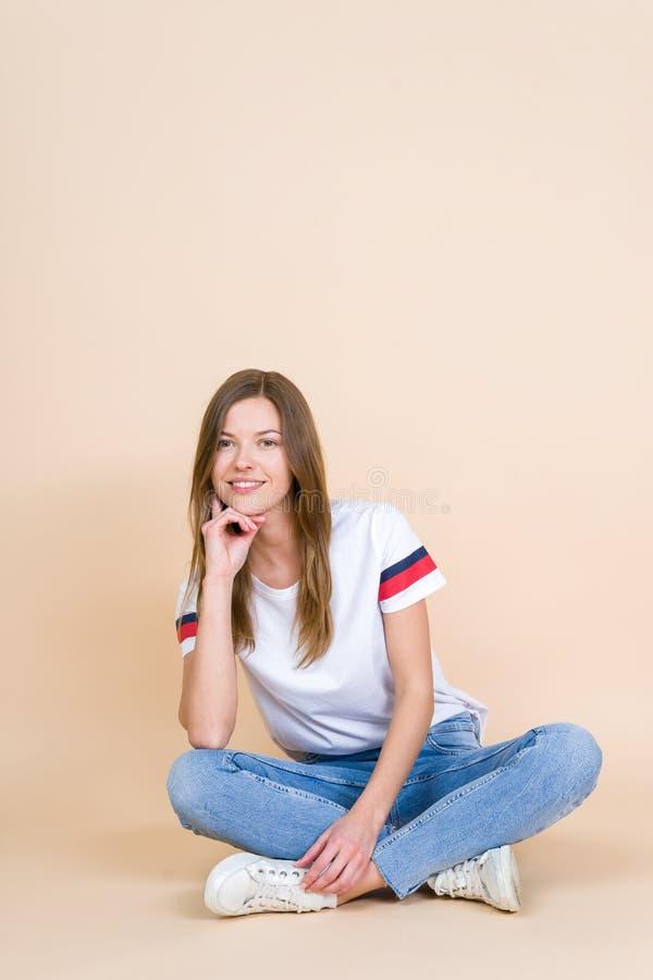 Jonge vrouw die met gekruiste benen op pastelkleur beige achtergrond zit royalty-vrije stock foto
