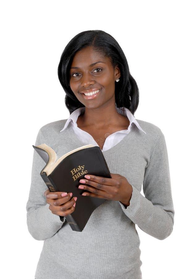 Jonge vrouw die met geopende bijbel glimlacht stock afbeelding