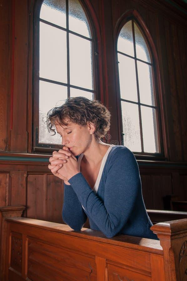 Jonge vrouw die met gesloten ogen in de kerk bidt stock afbeeldingen