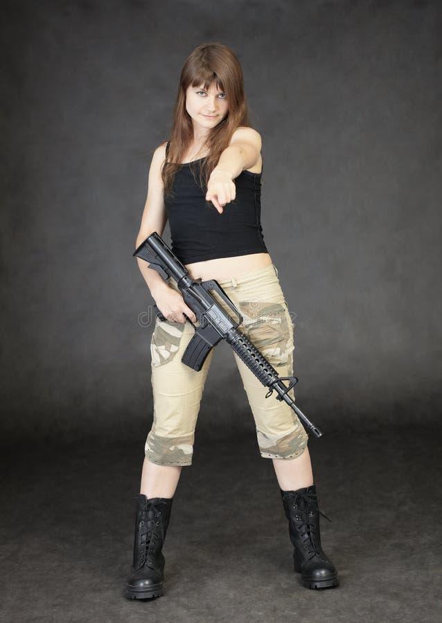 Jonge vrouw die met geweer status wordt bewapend royalty-vrije stock afbeeldingen