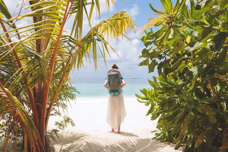 Jonge vrouw die met grote rugzak aan het strand in een tropische vakantiebestemming lopen stock afbeelding