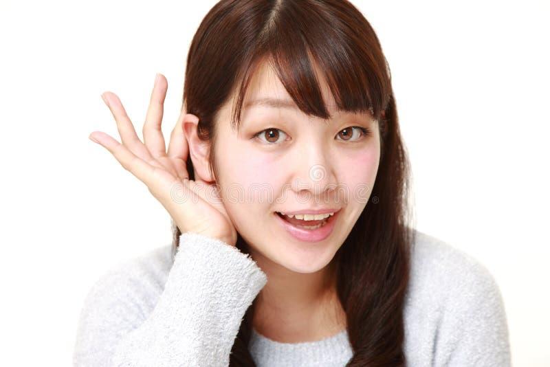Jonge vrouw die met hand achter oor dicht luisteren stock foto's