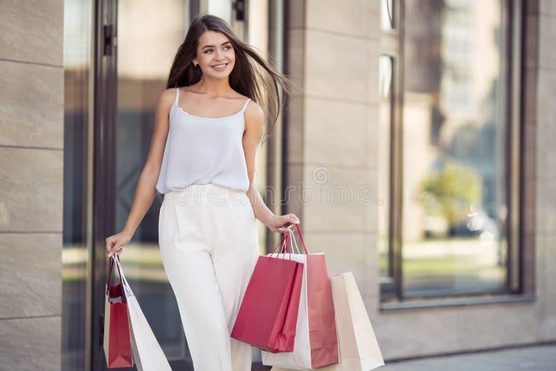 Jonge vrouw die met het winkelen zakken op straat lopen stock afbeeldingen