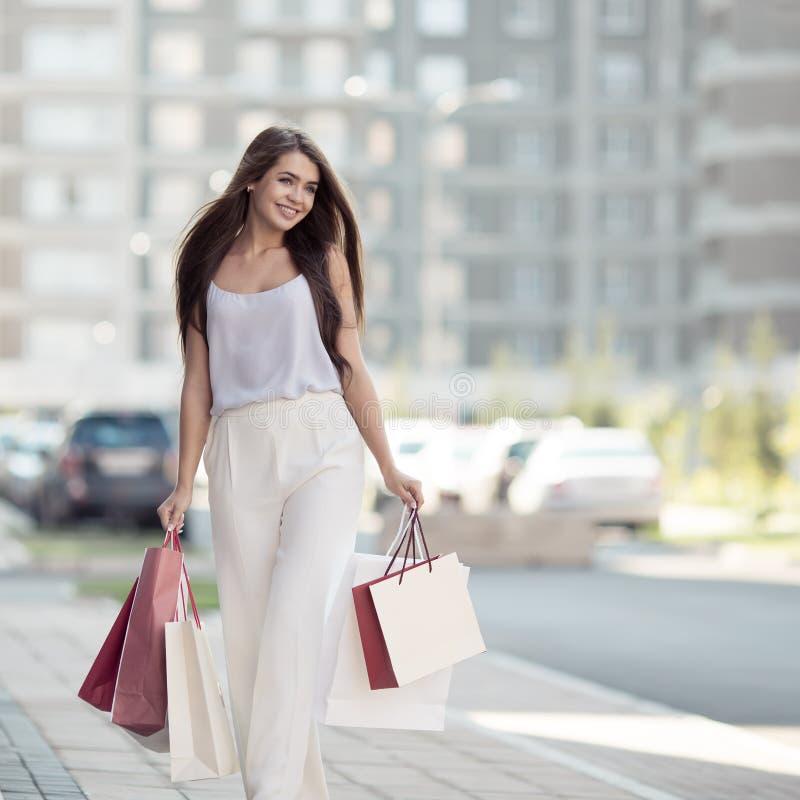 Jonge vrouw die met het winkelen zakken op straat lopen royalty-vrije stock foto
