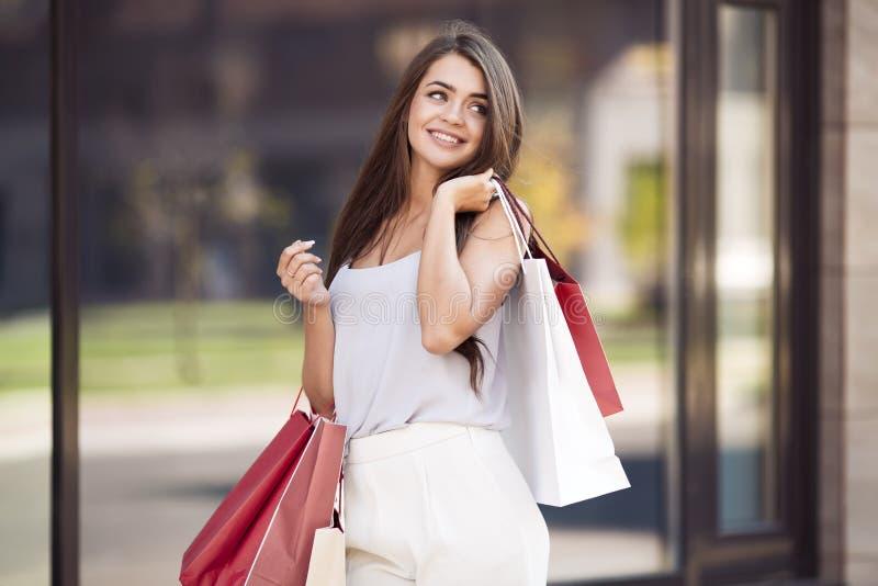 Jonge vrouw die met het winkelen zakken op straat lopen stock afbeelding