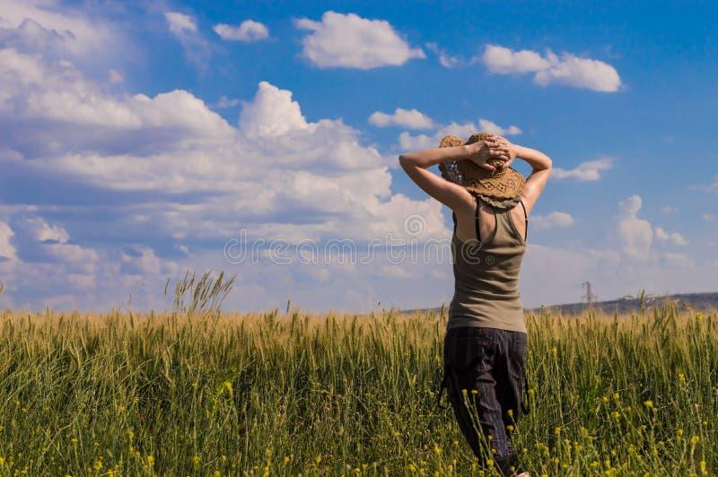 Jonge vrouw die met hoed van de aard genieten Het concept van de vrijheid stock afbeelding