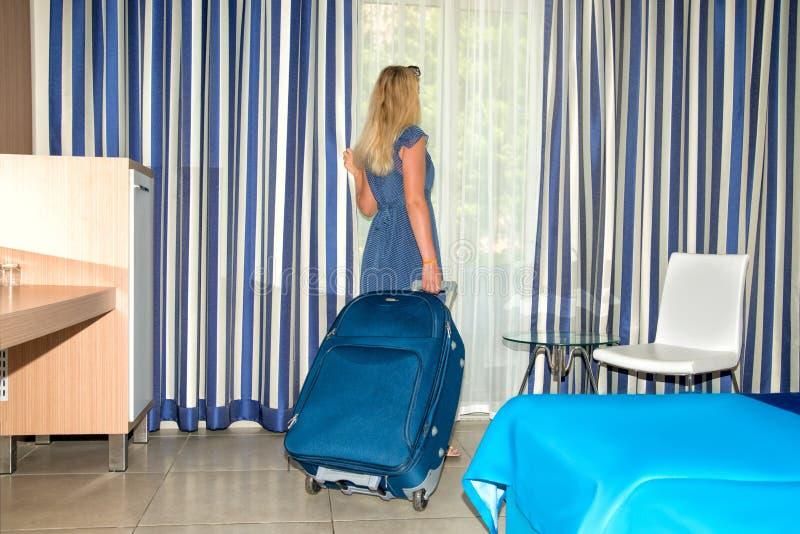 Jonge vrouw die met koffer uit het venster in de hotelruimte kijken Rust na een lange reis royalty-vrije stock fotografie