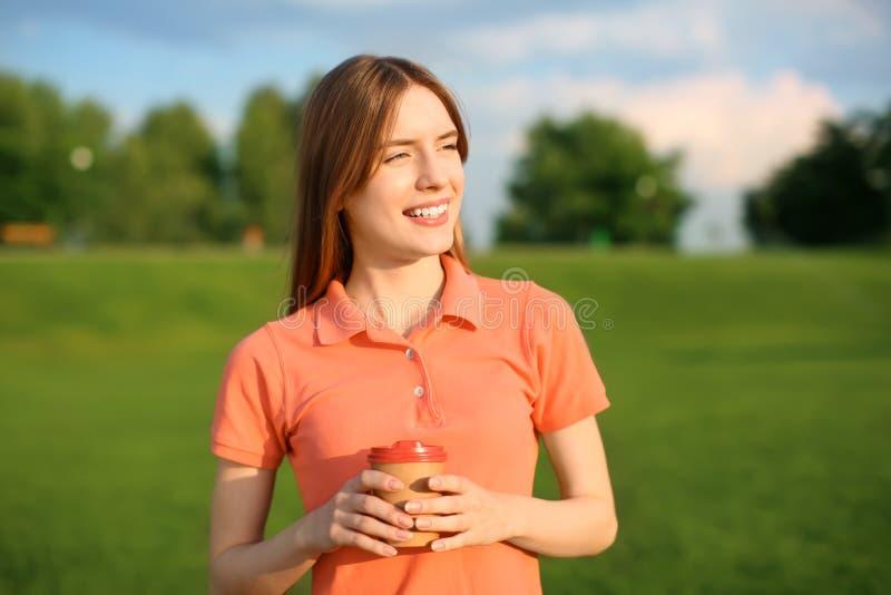 Jonge vrouw die met kop van koffie in park op zonnige dag rusten royalty-vrije stock foto's