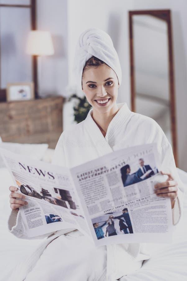 Jonge vrouw die met krant camera bekijken stock afbeelding