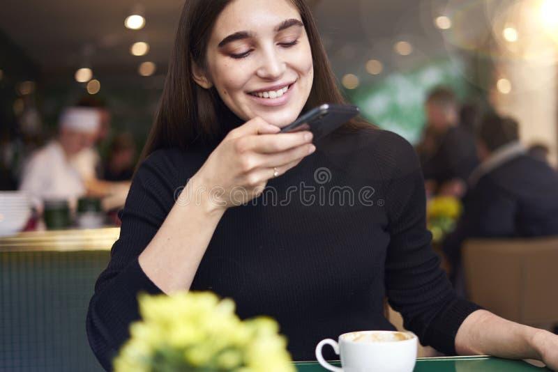Jonge vrouw die met lang haar foto maken door smartphone van kop van koffie, die rust in koffie hebben dichtbij venster royalty-vrije stock foto's