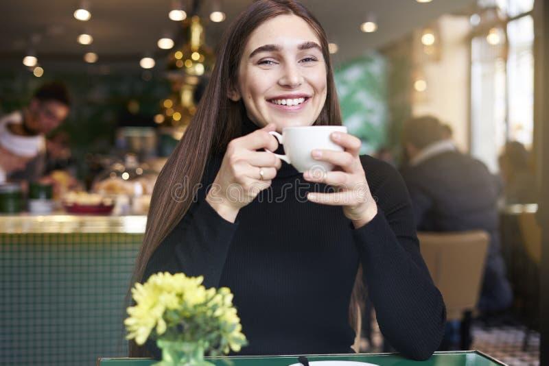 Jonge vrouw die met lang haar, het drinken kop van koffie in handen die rust in koffie hebben dichtbij venster glimlachen stock afbeelding
