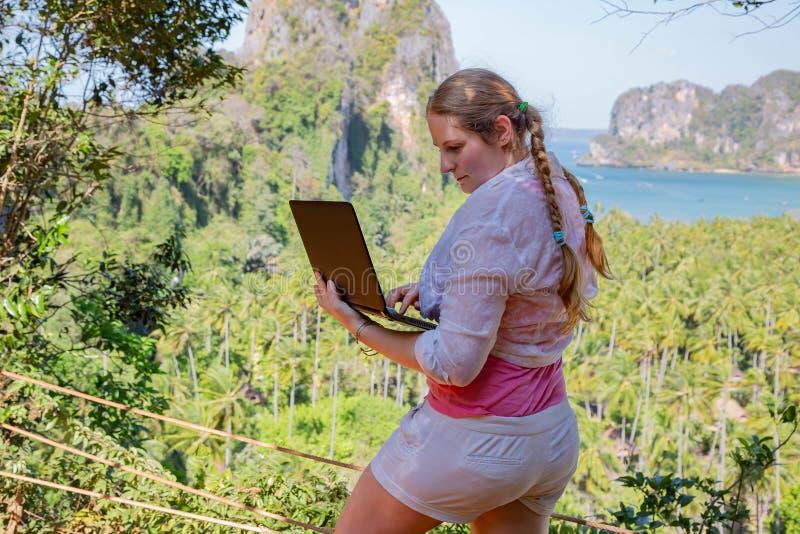 Jonge vrouw die met laptop aan een bovenkant van de berg met mening over overzees en tropisch strand werken Het werk en reis Onli stock fotografie