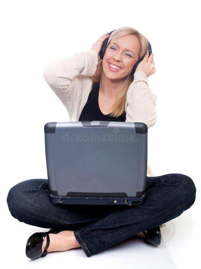 Jonge vrouw die met laptop aan muziek luistert stock foto's