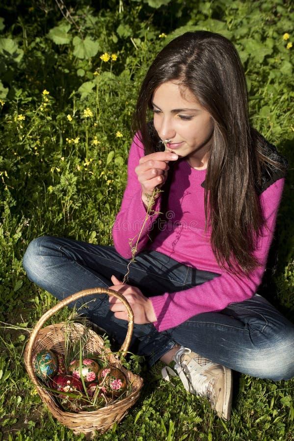 Jonge vrouw die met mand van eieren bloemen plukken stock afbeelding
