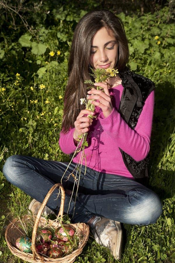 Jonge vrouw die met mand van eieren bloemen plukken stock fotografie