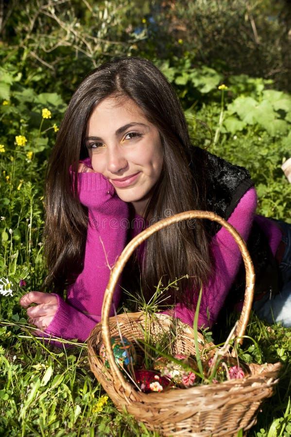 Jonge vrouw die met mand van eieren bloemen plukken stock foto's