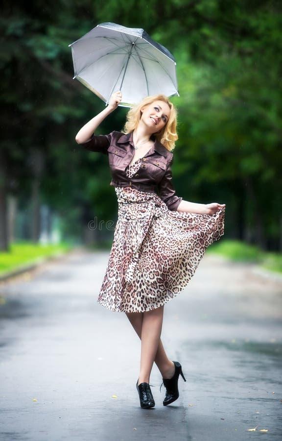 Jonge vrouw die met paraplu loopt royalty-vrije stock fotografie