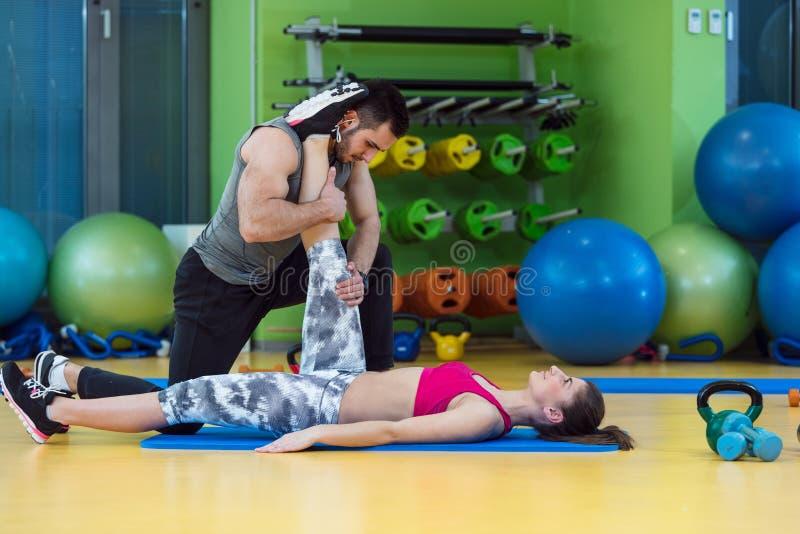 Jonge vrouw die met persoonlijke trainer bij de gymnastiek uitwerken royalty-vrije stock afbeeldingen
