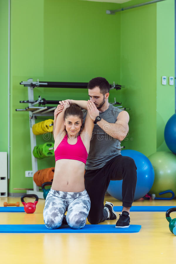 Jonge vrouw die met persoonlijke trainer bij de gymnastiek uitwerken royalty-vrije stock fotografie