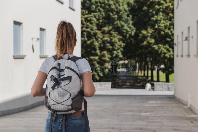 Jonge vrouw die met rugzak aan school na de zomervakantie lopen stock foto's