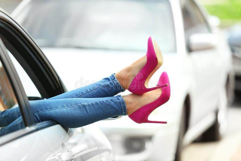 Jonge vrouw die met slanke benen in hoge hielen in auto ontspannen stock foto's