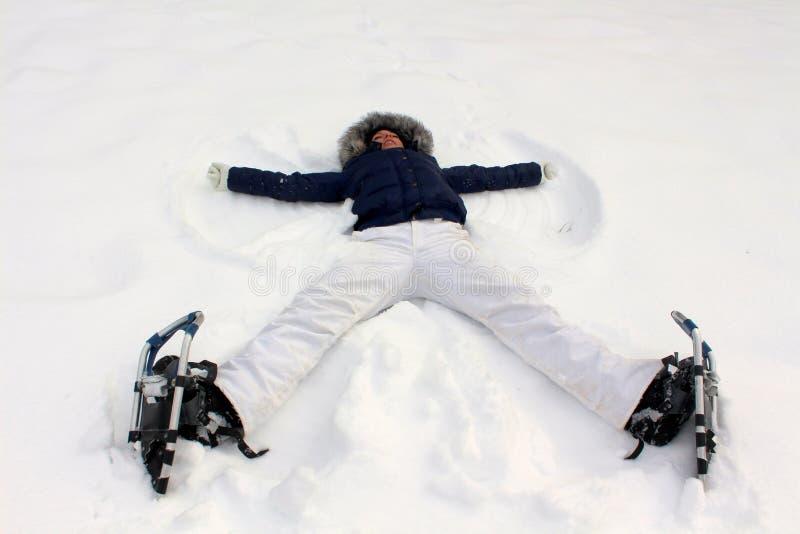 Jonge vrouw die met sneeuwschoenen engelen maken stock afbeelding