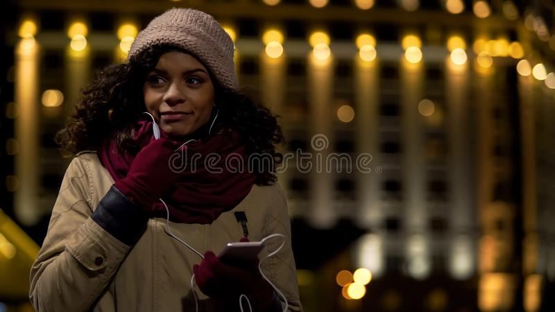 Jonge vrouw die met vriend over telefoon door hoofdtelefoons spreken, mededeling stock afbeelding