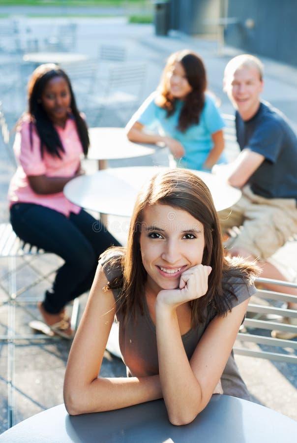 Jonge vrouw die met vrienden glimlacht stock foto