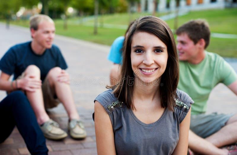 Jonge vrouw die met vrienden glimlacht stock foto's