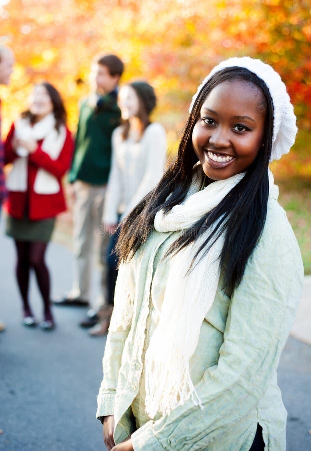 Jonge vrouw die met vrienden op de achtergrond glimlachen stock foto's