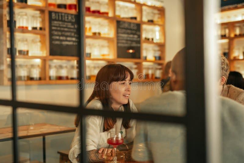 Jonge vrouw die met vrienden over dranken in een bar spreken stock foto