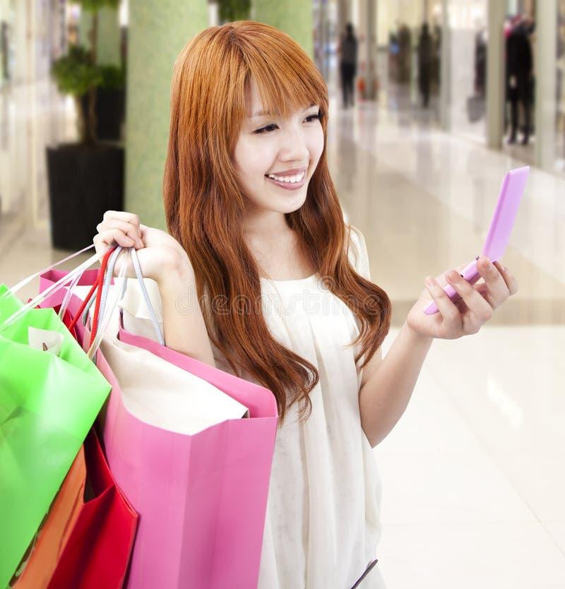 Jonge vrouw die mobiele telefoon en het winkelen zak houdt royalty-vrije stock afbeeldingen