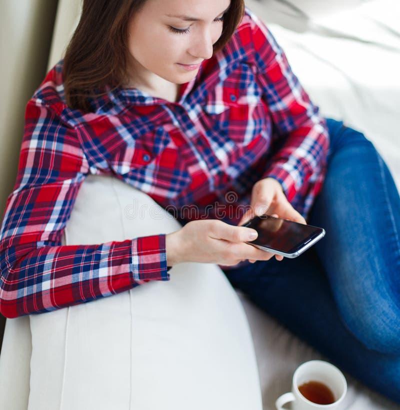 Jonge vrouw die mobiele telefoon met behulp van die thuis bij bank het ontspannen zitten royalty-vrije stock foto