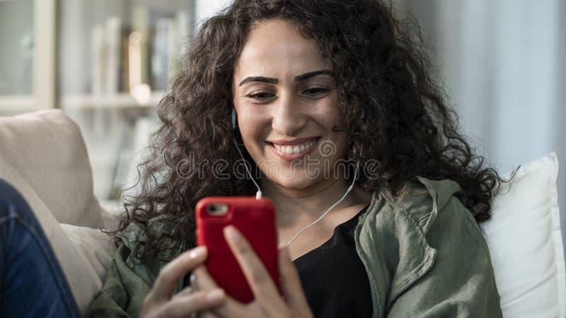 Jonge vrouw die mobiele telefoon thuis met behulp van royalty-vrije stock foto