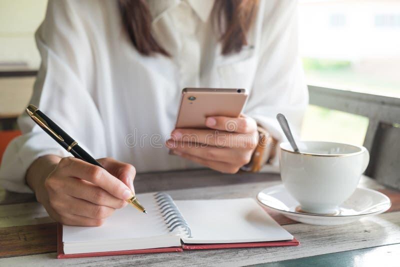 Jonge vrouw die mobiele telefoon voor het controleren van iets met behulp van terwijl greep stock afbeelding