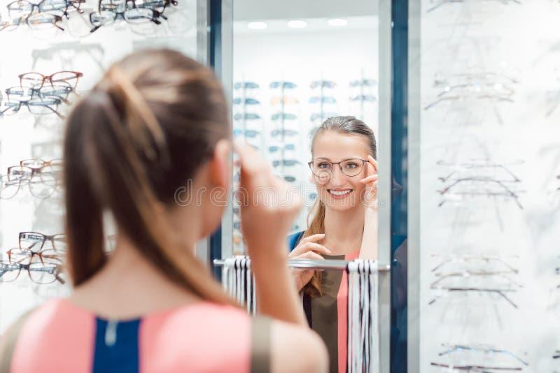 Jonge vrouw die modieuze glazen in optometristopslag proberen royalty-vrije stock foto