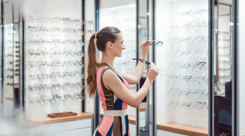 Jonge vrouw die modieuze glazen in optometristopslag proberen stock foto's