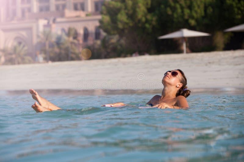 Jonge vrouw die in mooie overzees zwemmen stock afbeelding